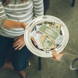 Shows a woman passing a collection plate filled with money back to a man in church.
